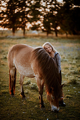 Smiling girl hugging pony - p312m2237453 by Anna Johnsson