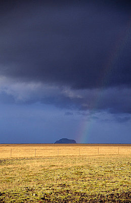 Fields of withered grass seperated with barbed wire fence, mountain in the distance and a rainbow, dark clouds above.  - p3483839 by Hakon Agustsson