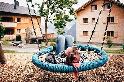 Teenage girl lying on hammock swing in playground using smartphone, Bludenz, Vorarlberg, Austria - p429m1105796 by JFCreatives