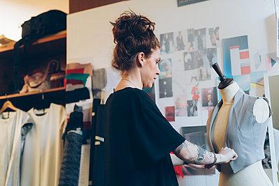 Fashion designer pinning garment onto dressmaker's dummy - p429m2058345 by Eugenio Marongiu