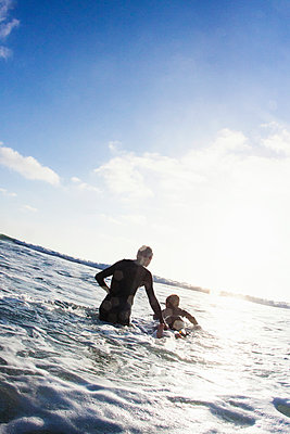 Father and son with surfboard on sea - p429m884150 by Yew! Images