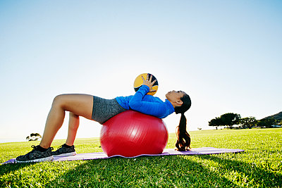 Mixed Race woman exercising with fitness ball and heavy ball in sunny field - p555m1472929 by Peathegee Inc