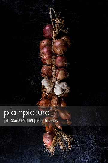 High angle close up of string of onions and garlic on black background. - p1100m2164865 by Mint Images