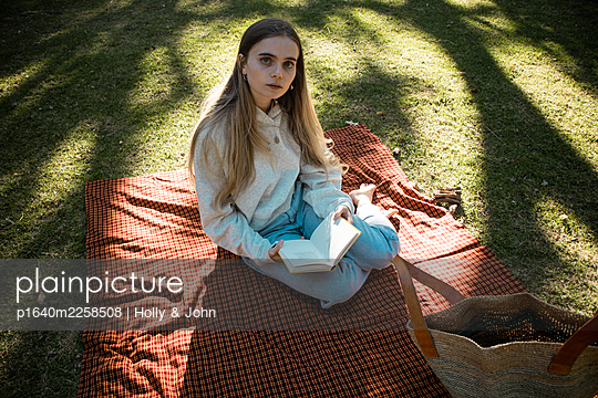 Teenage girl sits on picnic blanket reading a book - p1640m2258508 by Holly & John