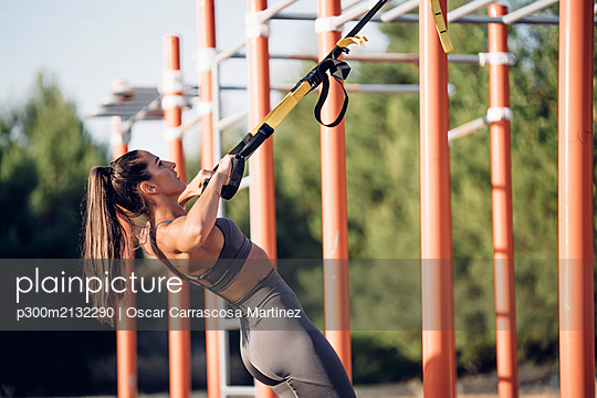 Young woman doing workout on calisthenics bars - p300m2132290 by Oscar Carrascosa Martinez