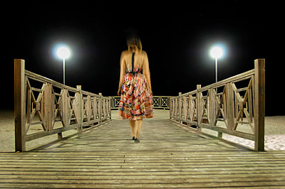 Blurred woman in floral dress on wooden jetty - p1072m829406 by Neville Mountford-Hoare
