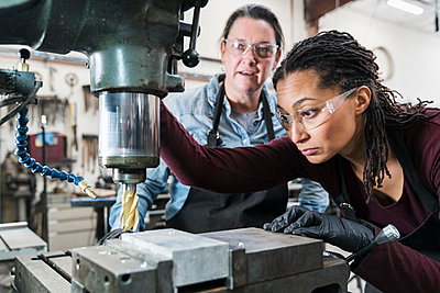 Two women wearing safety glasses standing in a metal workshop, working on metal drilling machine. - p1100m1544248 by Mint Images