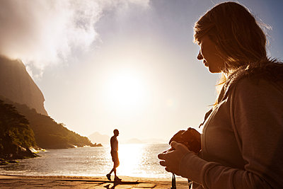 Woman holding camera while man standing by sea against sky - p1166m1098634f by Cavan Images