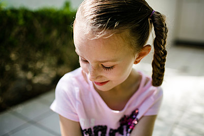 Close-up of shy girl standing at park - p1166m2025209 by Cavan Images
