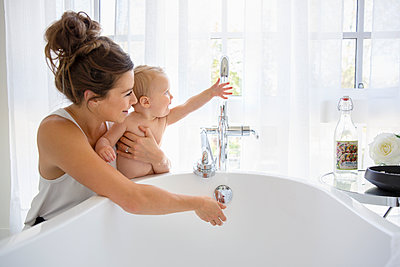 Mother and baby daughter preparing bath - p1192m2047646 by Hero Images