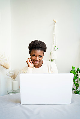 Young female entrepreneur working on laptop at home - p300m2257180 by Rafa Cortés