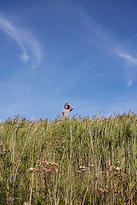 Young woman on beach with its dunes and marram grass - p341m1480673 by Mikesch