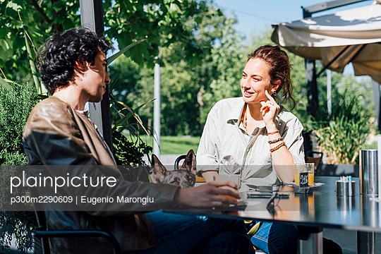 Smiling girlfriend talking to boyfriend while sitting at sidewalk cafe - p300m2290609 by Eugenio Marongiu