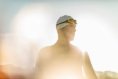 A swimmer in a wet suit, swimming hat and goggles.  - p1100m1112330f by Mint Images