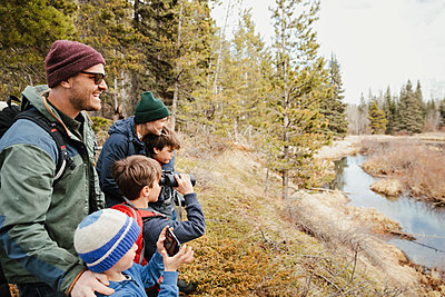 Family with binoculars hiking in sunny woods - p1192m2094196 by Hero Images