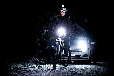 Cyclist followed by car at night in winter - p1687m2278817 by Katja Kircher
