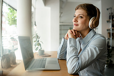 Businesswoman with laptop and headphones in a cafe - p300m2140468 by Kniel Synnatzschke