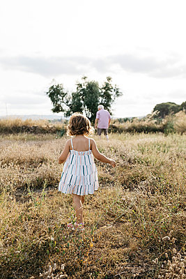 Grandfather and granddaughter walking on grassy land against sky - p300m2206780 by Josep Rovirosa
