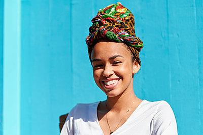Smiling woman wearing headscarf sitting against blue wall - p300m2266617 by Kiko Jimenez