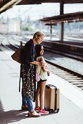 Smiling mother and daughter waiting on platform at train station - p426m2146082 by Maskot