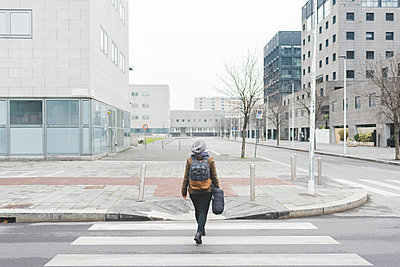 Rear view of female backpacker walking over city pedestrian crossing - p924m1446995 by Eugenio Marongiu