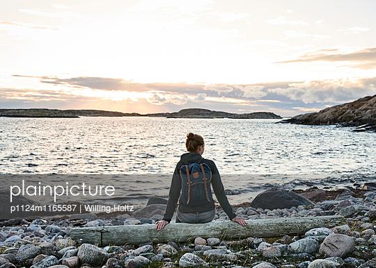 Frau sitzt auf Treibholz am Strand - p1124m1165587 von Willing-Holtz