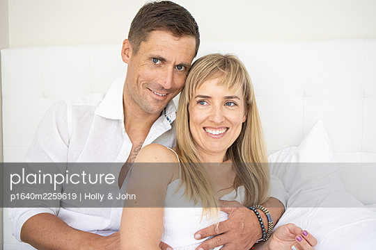 Happy couple sitting on bed, portrait - p1640m2259619 by Holly & John