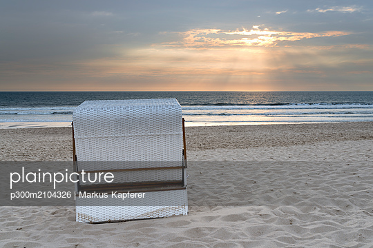 Germany, Sylt, North Sea, sandy beach with hooded beach chair in sunset - p300m2104326 by Markus Kapferer