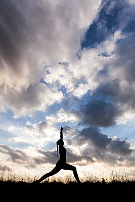Frau beim Yoga-Training als Silhouette vor bewölktem Himmel - p105m1181535 von André Schuster