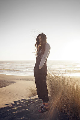 Woman with hands in pockets standing at beach against clear sky - p1166m1210487 by Cavan Images