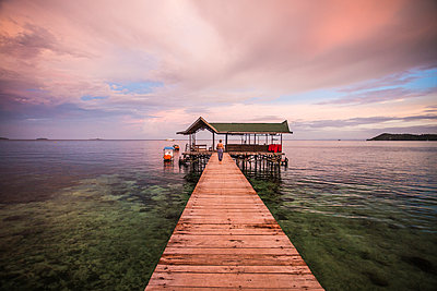 Distant view of woman on pier against cloudy sky - p1166m1488967 by Cavan Images