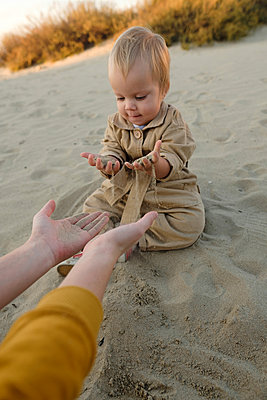 Woman with baby are playing on beach  - p1363m2142794 by Valery Skurydin