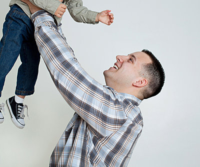 Young man holding son in the air, studio shot - p92412075 by Samantha Mitchell