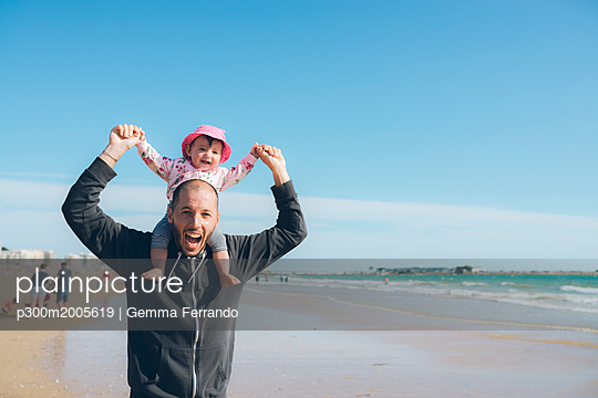 France, La Baule, portrait of father carrying his little daughter on shoulders on the beach - p300m2005619 von Gemma Ferrando