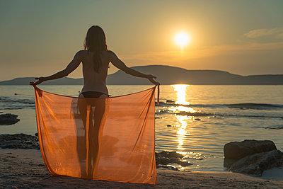 Eine Frau hält an einem Strand ein orangefarbenes Tuch hinter sich ausgestreckt im Gegenlicht der untergehenden Sonne - p1400m1475084 von Bastian Fischer