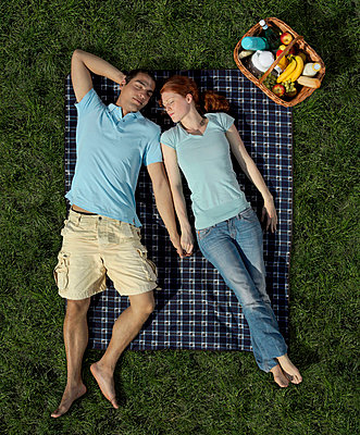 A young couple sleeping on a blanket in the park - p3018281f by Antenna photography
