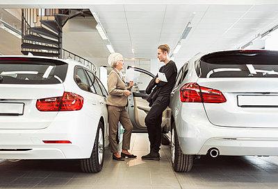 Full length of senior saleswoman talking to male customer at car dealership - p426m1036578f by Maskot