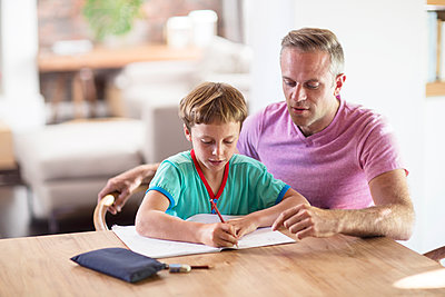 Caucasian father and son drawing at table - p555m1412706 by Resolution Productions
