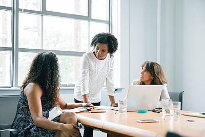 Businesswomen using laptop in meeting - p555m1504110 by John Fedele