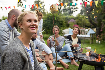 Roasting marshmallows in the garden - p788m1165260 by Lisa Krechting