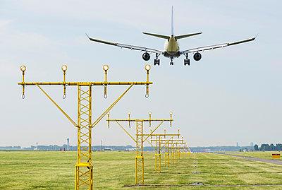 Airplane landing by runway landing lights, Schiphol, North Holland, Netherlands, Europe - p924m1480505 by Mischa Keijser