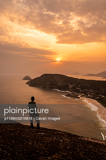 Beautiful sunset view to adventure photographer on hill top - p1166m2216818 by Cavan Images