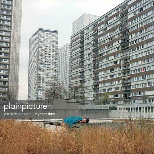 A woman at the bottom of a block of flats - p1610m2257892 by myriam tirler