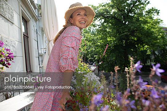 Blonde woman on her balcony - p1678m2258840 by vey Fotoproduction