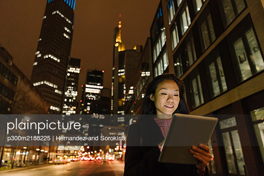 Young woman using tablet in the city at night, Frankfurt, Germany - p300m2188225 by Hernandez and Sorokina