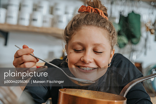 Happy chef tasting Broth soup while standing in kitchen - p300m2256361 by Mareen Fischinger
