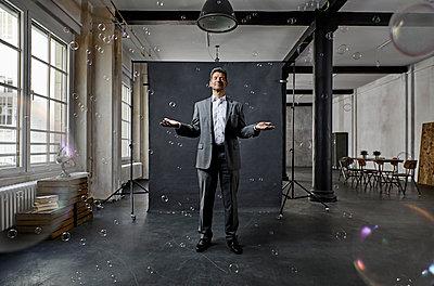 Mature businessman with bubbles standing in front of black backdrop in loft - p300m1580868 von Philipp Dimitri