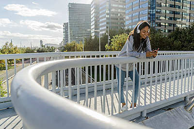 Young woman standing on a bridge, listening music, using smartphone - p300m2079782 by Giorgio Fochesato