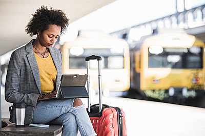 Young businesswoman using tablet at the train station - p300m2160725 by Uwe Umstätter