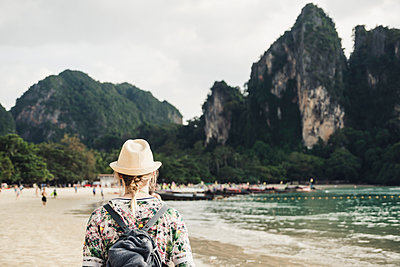 Woman looking at rock on the beach of Railay, Krabi, Thailand - p300m2166280 by Christophe Papke